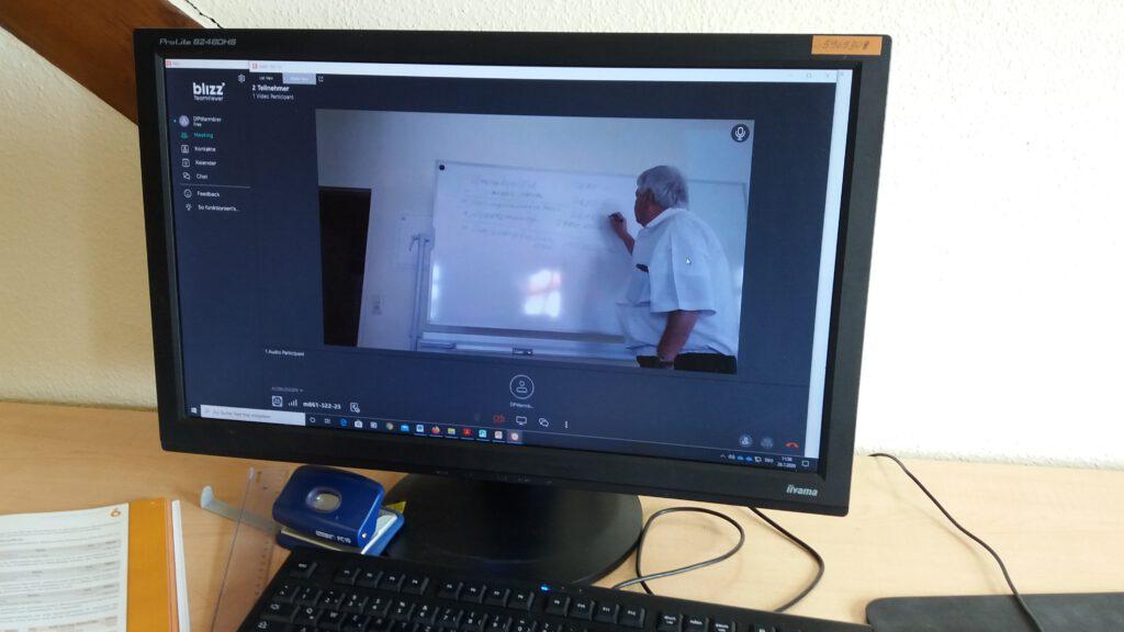 Computerbildschirm zeigt Lehrkraft beim Onlineunterricht per Video